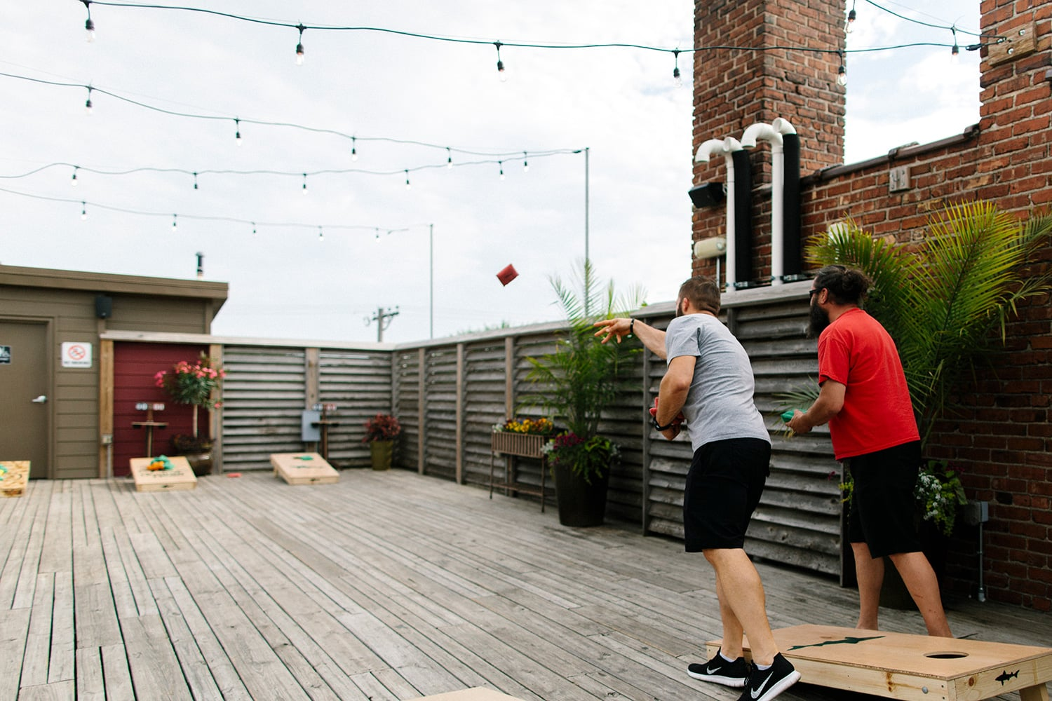 guys-playing-cornhole-on-rooftop